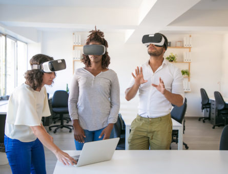 Diverse team of three watching virtual presentation. Man and women wearing virtual reality glasses, standing in office, using laptop, touching air. Teamwork concept
